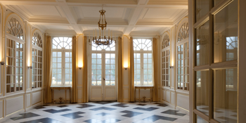 spiegelzaal met vloer met tegels in zwart en wit en zicht op het balkon